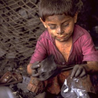 Tonio Jorge, 6 år, i El Salvador fyller små plastpåsar med kol som hans familj säljer på marknaden där de bor. UNICEF/Donna DeCesare
